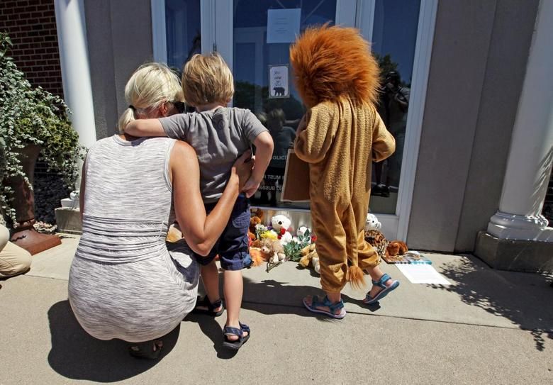 Sarah Madison (L) holds her son Beckett, 3, as her daughter Quinn, 5 (in costume), look at stuffed animals at the doorway of River Bluff Dental clinic in protest against the killing of ''Cecil'' a famous lion in Zimbabwe, in Bloomington, Minnesota July 29, 2015.  REUTERS/Eric Miller