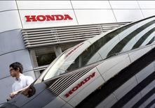 Мужчина у салона Honda Motor Co в Токио. 31 июля 2015 года. Японский автопроизводитель Honda Motor Co сообщил в пятницу о росте квартальной чистой прибыли на 20 процентов за счет хороших продаж на крупнейшем для компании североамериканском рынке и слабой иены, компенсировавшей рост затрат, связанных с качеством. REUTERS/Yuya Shino