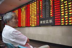 Un inversor mira un tablero electrónico que muestra la información de las acciones, en una correduría en Nanjing, provincia de Jiangsu, China, 30 de julio de 2015. Las bolsas de Asia avanzaban el viernes, pero aún se encaminan a reportar una pérdida en julio, lastradas por la mayor caída mensual de las acciones chinas en seis años. REUTERS/China Daily
