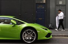 A man walks past an Italian sports car in Shoreditch, London, April 16, 2015. REUTERS/Cathal McNaughton