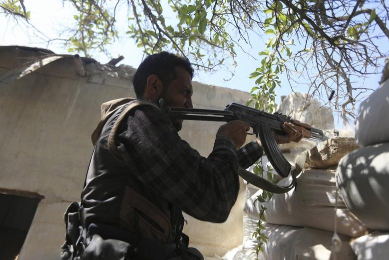A fighter from the Free Syrian Army's Al Rahman legion fires his weapon on the frontline against the forces of Syria's President Bashar al-Assad in Jobar, a suburb of Damascus, Syria July 27, 2015. REUTERS/Bassam Khabieh