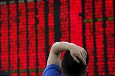 Un hombre mira un tablero electrónico que muestra la información de las acciones en una correduría en Beijing, China, 1 de julio de 2015. El regulador de valores de China congeló una cuenta comercial ligada a Citadel Securities, una unidad del grupo estadounidense que también es propietaria del fondo de cobertura Citadel LLC, en momentos en que Pekín enfrenta a los especuladores para apuntalar al mercados bursátil local. REUTERS/Kim Kyung-Hoon