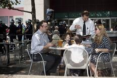 Una familia en un restaurant mientras activistas de Ocuppy Wall Street protestas por las calles del distrito financiero de Nueva York, 17 de septiembre de 2012. El crecimiento del sector servicios de Estados Unidos mejoró modestamente en julio frente a junio, debido a un ligero repunte del empleo y de los nuevos negocios, mostró el miércoles un reporte sectorial. REUTERS/Andrew Burton