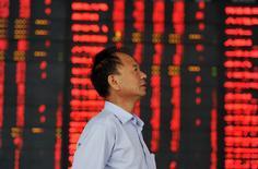 Homem em frente painel com cotações da bolsa de valores, na China.  04/08/2015   REUTERS/China Daily
