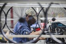 Un empleado opera una maquina de encaje de ruedas, en la planta de Bicycle Corporation of America, en Manning, Carolina del Sur, 19 de noviembre de 2014. El empleo en Estados Unidos subió a un ritmo sólido en julio y los salarios repuntaron tras el sorpresivo estancamiento del mes anterior, señales de que la mejoría de la economía podría abrir las puertas a un alza de tasas de interés de la Reserva Federal en septiembre. REUTERS/Randall Hill
