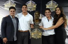 Aug 8, 2015; Canton, OH, USA; The children of Junior Seau (not pictured), Tyler Seau and Jake Seau and Hunter Seau and Sydney Seau pose with the bust of their father during the 2015 Pro Football Hall of Fame enshrinement at Tom Benson Hall of Fame Stadium. Kirby Lee-USA TODAY Sports