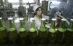 Женщина работает пивоваренном заводе Taedonggang Beer в Пхеньяне 3 мая 2004 года. Вниманию самых рисковых инвесторов: Северная Корея ищет за рубежом желающих вложить $39 миллионов в новую пивоварню в Вонсане, портовом городе, на который у всенародного лидера Ким Чен Ына есть амбициозные планы. REUTERS/Lee Jae-Won