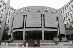 Una persona camina frente a la sede del Banco Popular Chino, en Beijing, 25 de junio de 2013. Los bancos chinos extendieron 1,48 billones de yuanes (238.400 millones de dólares) en nuevos préstamos en julio, una cantidad sorprendentemente robusta, pero los economistas dijeron que las cifras pueden haber sido distorsionadas por un paquete de rescate de Pekín para el golpeado mercado de valores. REUTERS/Jason Lee