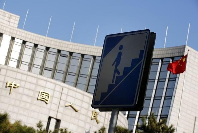A sign for pedestrians is seen in front of the headquarters of the People's Bank of China, China's central bank, in central Beijing November 24, 2014. REUTERS/Kim Kyung-Hoon