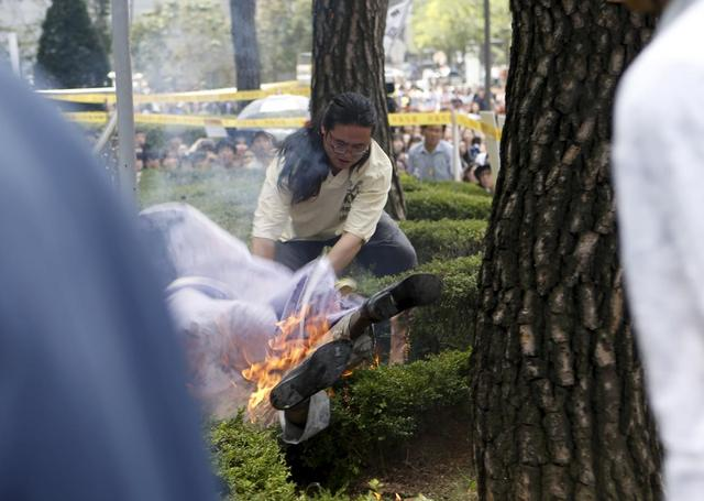 A man attempts to put out flames from another man (bottom) who set himself on fire during a weekly anti-Japan rally to demand for an official apology and compensation from the Japanese government in front of the Japanese embassy in Seoul, South Korea, August 12, 2015. REUTERS/Kim Hong-Ji