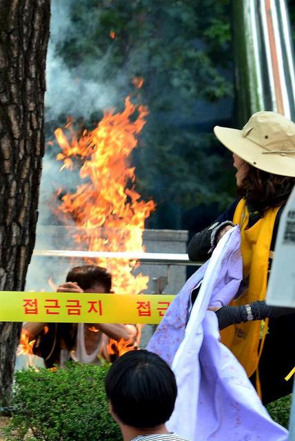 A man sets himself on fire during a weekly anti-Japan rally to demand for an official apology and compensation from the Japanese government in front of the Japanese embassy in Seoul, South Korea, August 12, 2015.   REUTERS/Son Hyung-ju/News1
