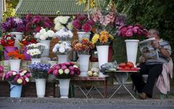 Торговец цветами в Подмосковье 10 августа 2015 года. Начав со сжигания ввезенных в обход запрета западных продуктов, возмутившего многих в пережившей голод стране, российские власти  стали подбрасывать в огонь голландские цветы. REUTERS/Sergei Karpukhin
