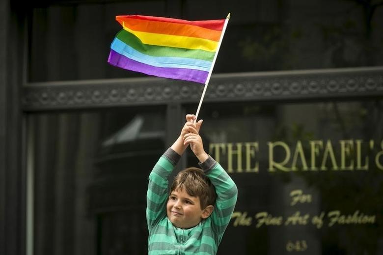 A young boy waves a rainbow flag while watching the San Francisco gay pride parade two days after the U.S. Supreme Court's landmark decision that legalized same-sex marriage throughout the country in San Francisco, California June 28, 2015. REUTERS/Elijah Nouvelage