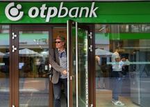 Мужчина выходит из отделения OTP Bank в Будапеште. 15 августа 2014 года. Венгерский OTP Bank вернулся к прибыли во втором квартале 2015 года, так как снижение стоимости риска на проблемных российском и украинском рынках компенсировало высокие налоги и небольшое сокращение операционного дохода. REUTERS/Laszlo Balogh