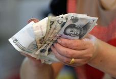 Un vendedor sostiene yuanes en un mercado en Beijing, 12 de agosto de 2015. El yuan chino operaba estable frente al dólar el viernes, pero registró su mayor pérdida semanal a la fecha debido a la decisión sorpresiva del banco central de devaluar a la moneda. REUTERS/Jason Lee