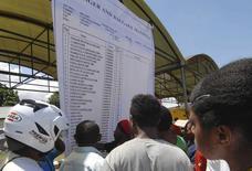 Люди изучают список пассажиров разбившегося самолета Trigana Air Service в аэропорту Сентани близ Джаяпуры. 17 августа 2015 года. Индонезийский пассажирский самолет с 54 людьми на борту, разбившийся в гористой местности в провинции Папуа, перевозил около $470.000 наличными, которые предназначались для жителей отдаленных селений, сообщил в понедельник представитель почтовой службы. REUTERS/Lucky R/Antara Foto