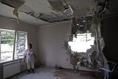 Женщина в своей квартире, пострадавшей от обстрелов, в пригороде Донецка. 16 августа 2015 года. Несколько мирных жителей погибли под артиллерийским огнем во вспыхнувших за ночь перестрелках по обе стороны линии фронта на востоке Украины, сообщили в понедельник власти Украины и сепаратисты. REUTERS/Alexander Ermochenko