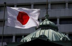 Una bandera de Japón ondea sobre el edificio del Banco de Japón en Tokio, 22 de mayo de 2015. La economía de Japón se contrajo a una tasa anualizada de 1,6 por ciento en el período abril-junio, debido a una fuerte caída en las exportaciones y a que los consumidores redujeron su gasto, en un mal augurio para la política del primer ministro Shinzo Abe que busca sacar al país de décadas de deflación. REUTERS/Toru Hanai