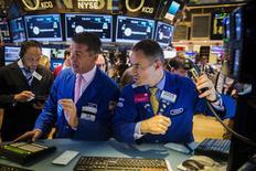 Трейдеры на фондовой бирже в Нью-Йорке. 22 июля 2015 года. Уолл-стрит выросла в понедельник, поскольку сильные экономические данные поддержали жилищный сектор, а инвесторы активно покупали акции биотехнологических компаний и медиакомпаний. REUTERS/Lucas Jackson