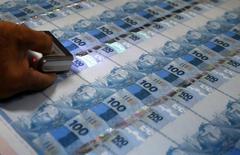Funcionário inspeciona notas de 100 reais recém impressas na Casa da Moeda, no Rio de Janeiro. 23/08/2012 REUTERS/Sergio Moraes