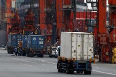 Personas trabajan cerca de contenedores en un puerto en Tokio, 17 de junio de 2015. El crecimiento de las exportaciones de Japón se desaceleró en julio debido a menores envíos de vehículos y aparatos electrónicos a Asia, en una señal de que el panorama de la demanda global podría estar perdiendo brillo. REUTERS/Yuya Shino