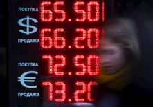 """Женщина проходит мимо табло пункта обмена валюты в Москве 18 августа 2015 года. Банк России сообщил, что в сценарии со снижением цен на нефть Urals со $110 до $55 потенциальный ВВП России в 2015-2017 годах может снизиться суммарно на 4,2-4,8 процента в течение двух лет после нефтяного шока и закрытия внешних рынков, а то ослабление рубля, которое наблюдается, - остаточные явления """"естественного"""" процесса подстройки экономики. REUTERS/Maxim Shemetov"""