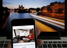 Una imagen de ilustración muestra un apartamento en París ofrecido por la actriz estadounidense Judith Freiha en la aplicación de Airbnb es vista en la pantalla de un móvil delante de la panorámica del río Siena proyectada en un portátil, en Francia, el 9 de agosto de 2015. La compañía de alquiler online de viviendas Airbnb dijo que estaba estableciendo una alianza con los fondos de inversión China Broadband Capital y Sequoia China para expandirse en el mercado chino y encontrar a un presidente ejecutivo para sus operaciones en el país. REUTERS/Christian Hartmann