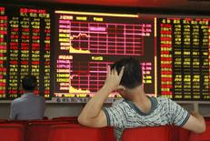 Inversores miran un tablero electrónico que muestra la información de las acciones en una correduría en Haikou, China, 19 de agosto de 2015.   Los principales índices bursátiles de China caían más de un 1 por ciento en las primeras operaciones del jueves, ignorando la intervención del Gobierno en la sesión previa. REUTERS/Stringer