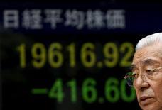 Un peatón camina junto a un tablero electrónico que muestra el índice Nikkei afuera de una correduría en Tokio, Japón, 21 de agosto de 2015. El índice Nikkei de la Bolsa de Tokio cayó debajo de la marca de 20.000 unidades por cuarto día consecutivo el viernes, al mínimo en tres meses y medio, por el surgimiento de nuevas señales de desaceleración de la economía china. REUTERS/Yuya Shino