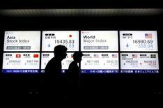 Peatones caminan junto a un tablero electrónico que muestra el precio de las acciones de varios países del mundo, afuera de una correduría en Tokio, 21 de agosto de 2015. Los mercados de acciones globales se desplomaban el viernes, apuntando a su peor semana del año, mientras las materias primas sufrían una nueva golpiza después de otra serie de datos alarmantes de China que impulsaron a los inversores a la seguridad de los bonos y el oro. REUTERS/Issei Kato