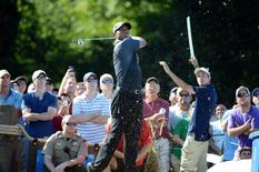 Tiger Woods (center) hits his tee shot on the 16th hole during the second round of the Wyndham Championship golf tournament at Sedgefield Country Club. Mandatory Credit: Rob Kinnan-USA TODAY Sports
