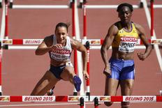 Jessica Ennis-Hill of Britain (L) and Akela Jones of Barbados compete during the 100 metres hurdles event of the women's heptathlon at the 15th IAAF World Championships at the National Stadium in Beijing, China August 22, 2015.    REUTERS/David Gray
