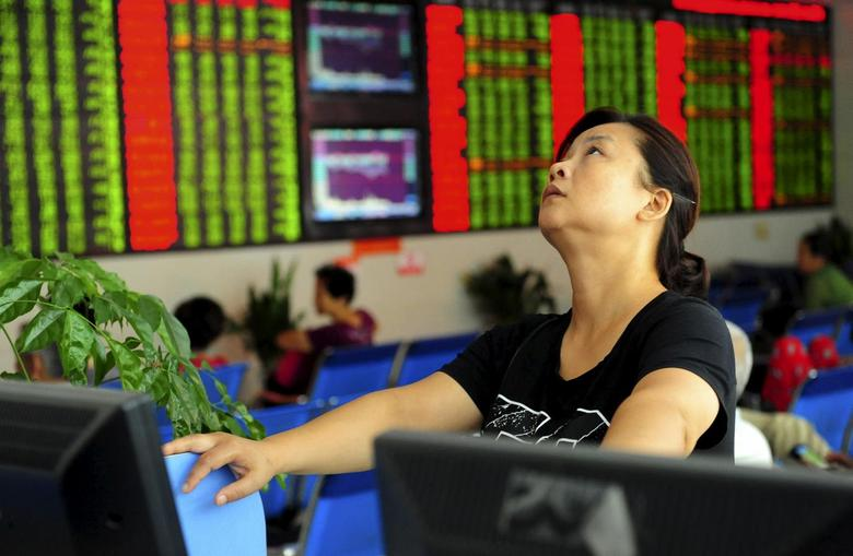 An investor looks up in front of an electronic board showing stock information at a brokerage house in Fuyang, Anhui province, China August 21, 2015. REUTERS/China Daily