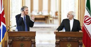 Министр иностранных дел Великобритании Филип Хаммонд (слева) на встрече с иранским коллегой Мохаммадом Джавадом Зарифом в Тегеране 23 августа 2015 года. Отмена санкций в отношении Ирана может начаться уже весной следующего года, сказал в понедельник министр иностранных дел Великобритании Филип Хаммонд.  REUTERS/Raheb Homavandi/TIMA