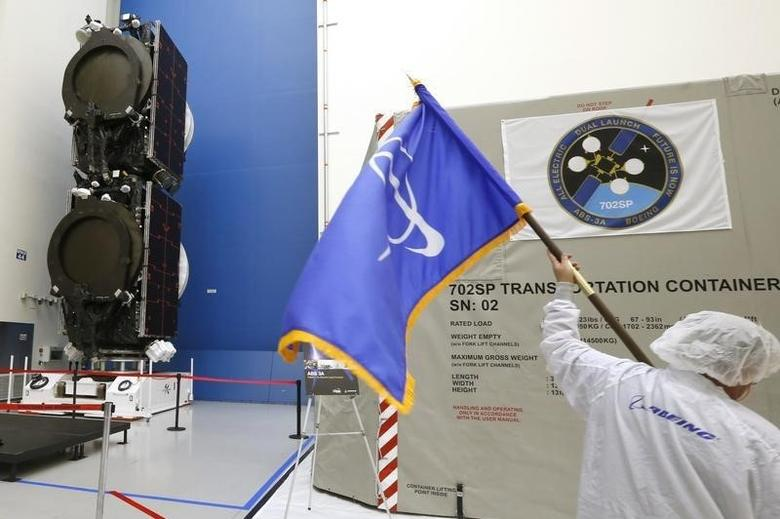 A man carries a flag with the Boeing logo past the world's first two all-electric propulsion 702SP satellites in the Boeing Satellite Development Center in El Segundo, California, January 9, 2015. REUTERS/Lucy Nicholson