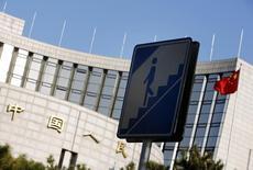 Дорожный знак на фоне здания ЦБ Китая в Пекине. 24 ноября 2014 года. Центробанк Китая во вторник сократил процентные ставки и требования к банковским резервам, чтобы поддержать стремительно падающий фондовый рынок и экономику. REUTERS/Kim Kyung-Hoon