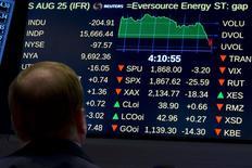 Трейдер смотрит на экран с котировками на фондовой бирже в Нью-Йорке. 25 августа 2015 года. Фондовые рынки США снизились во вторник из-за опасений инвесторов за состояние экономики Китая. REUTERS/Brendan McDermid