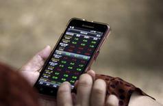 Investidora vê informações de ações em smartphone em Pequim. 26/08/2015 REUTERS/Jason Lee