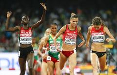 Hyvin Kiyeng Jepkemoi of Kenya reacts as she crosse the finish line next to Habib Ghribi of Tunesia and Gesa Krause (R) of Germany  the women's 3000m steeplechase final during the 15th IAAF World Championships at the National Stadium in Beijing, China August 26, 2015.  REUTERS/Lucy Nicholson
