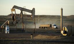 Un camión conduce junto a una unidad de bombeo de petróleo, en la Reserva índia de Fort Berthold, en Dakota del Norte, 1 de noviembre de 2014. Los inventarios del petróleo en Estados Unidos cayeron con fuerza la semana pasada ante menores importaciones, mientras que los de gasolina y destilados subieron pese a una reducción en las tasas de refinación, mostró el miércoles un informe de la gubernamental Administración de Información de Energía. REUTERS/Andrew Cullen