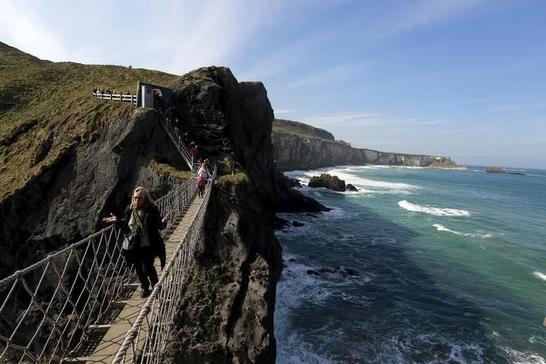 Tourists make their way across Carrick-a-Rede Rope Bridge on the Causeway coast, north of Belfast April 8, 2015. REUTERS/Cathal McNaughton