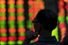 Investidor olhando monitor com cotações da bolsa de valores, em Xangai. 26/08/2015  REUTERS/Aly Song