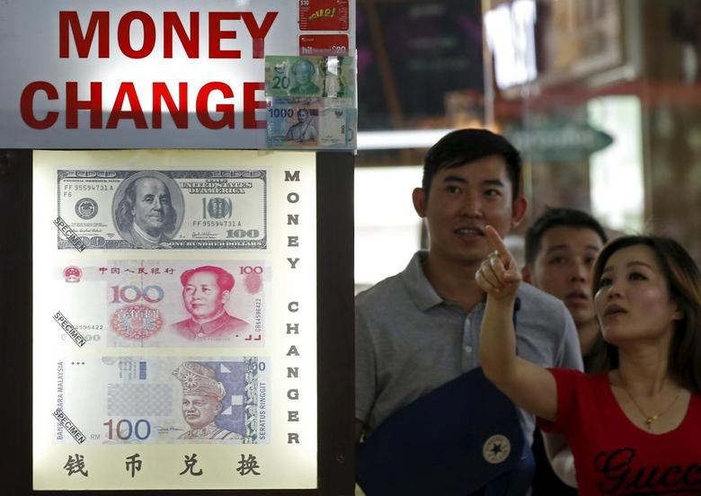 People look at the exchange rate at a moneychanger displaying a poster of U.S. dollar bill, Chinese Yuan and Malaysia Ringgit in Singapore August 24, 2015. REUTERS/Edgar Su