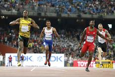 Usain Bolt of Jamaica (L) crosses the finish line ahead of Justin Gatlin (2nd R) from the U.S., Zharnel Hughes of Britain (2nd L) and Ramil Guliyev of Turkey in the men's 200m final during the 15th IAAF World Championships at the National Stadium in Beijing, China August 27, 2015. REUTERS/Lucy Nicholson