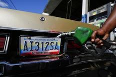 Un trabajador cargando combustible en una gasolinera en Caracas, ene 12 2015. Venezuela ha establecido contacto con miembros de la Organización de Países Exportadores de Petróleo (OPEP) para presionar para que se realice una reunión de emergencia que fije una estrategia que frene la caída de los precios del crudo, dijo el jueves el diario Wall Street Journal citando a personas cercanas al tema.      REUTERS/Jorge Silva