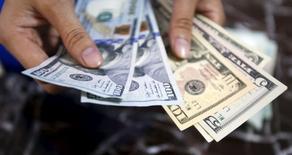 Un empleado revisa billetes de dólares estadounidenses, en un banco en Hanoi, Vietnam, 12 de agosto de 2015. El dólar operaba estable frente a una cesta de grandes monedas el viernes en la medida en que una sensación de calma volvía a los mercados financieros, poniendo fin a una semana agitada en que el billete verde tocó mínimos de siete meses frente al euro y al yen. REUTERS/Kham