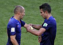 Robin Van Persie colocando a faixa de capitão em Arjen Robben, durante partida contra a Austrália na Copa do Mundo de 2014, no Brasil.   18/06/2015  REUTERS/Marko Djurica