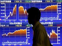 Un hombre camina frente a un gráfico que muestra el índice Nikkei, afuera de una correduría en Tokio, 25 de agosto de 2015. El índice Nikkei de la bolsa de Tokio el lunes cayó en medio de toma de ganancias luego de que la confianza de los inversores cedió por unos datos débiles de producción industrial y ante la incertidumbre sobre cuándo la Reserva Federal de Estados Unidos comenzará a subir las tasas de interés. REUTERS/Issei Kato
