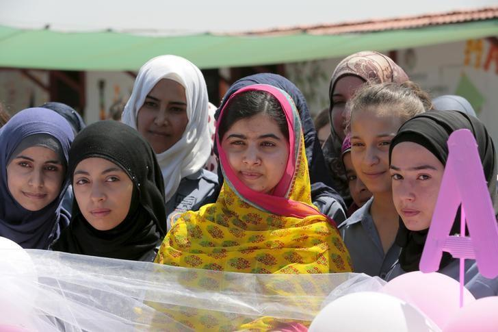 Nobel Peace Prize laureate Malala Yousafzai (C) poses with girls for a picture at a school for Syrian refugee girls, built by the NGO Kayany Foundation, in Lebanon's Bekaa Valley July 12, 2015. REUTERS/Jamal Saidi/Files