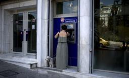 La stabilité politique et la recapitalisation réussie des banques grecques sont deux préalables à la levée des mesures de contrôle des capitaux prises en juin pour éviter l'effondrement du système financier en Grèce, soutient le président d'Eurobank, l'un des principaux établissements financiers du pays. /Photo prise le 19 août 2015/REUTERS/Stoyan Nenov
